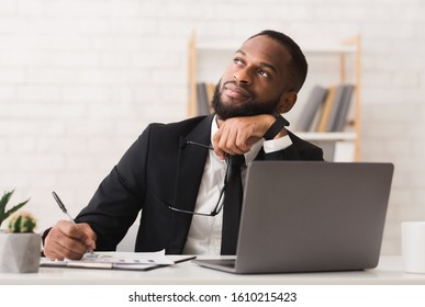 Dreamy afro entrepreneur thinking about his company future, making plans, copy space