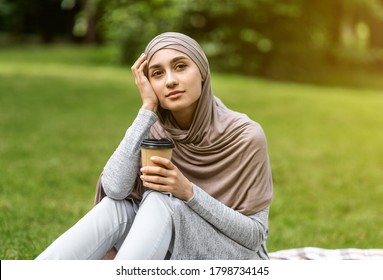 Dreamy arab girl sitting alone at public park, drinking coffee, looking at empty space