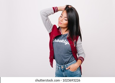 Dreamy asian female model with shiny hair enjoying photoshoot in white studio. Indoor portrait of romantic brunette girl with lightly-tanned skin posing in jeans and gray t-shirt.