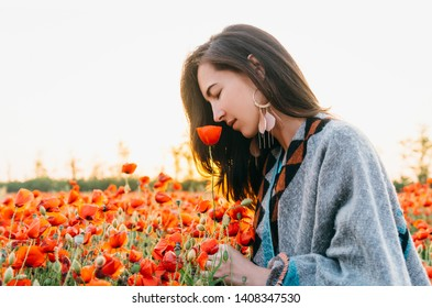 Dreamy attractive brunette young woman smelling a red poppy in flower meadow, summer vacations.