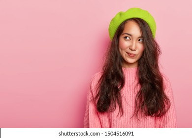 Dreamy beautiful Asian woman being deep in thoughts, looks aside and purses lips, wears green beret and knitted sweater, has tender look, isolated on pink wall, free space. Ethnicity, fashion concept