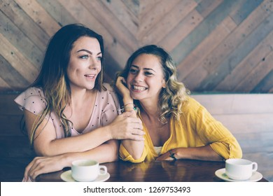 Dreamy beautiful girls discussing future plans and rumors. Young woman sharing news with her friend when drinking cappuccino in coffeeshop. Best friend concept