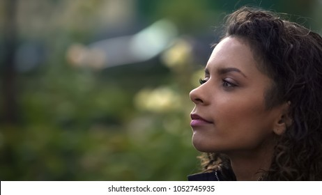 Dreamy biracial curly haired woman looking afar, thinking about life, closeup
