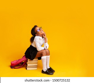 Dreamy Black Elementary School Girl Sitting On Stack Of Books On Yellow Background. Studio Shot, Free Space For Text