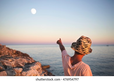 dreamy boy points his finger with the moon in the sky at sea