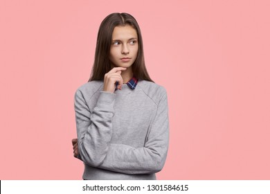 Dreamy brunette girl smiles gently, keeps hand together under chin. Teenager looks aside, stands against pink background with copy space left for your advertisement or information.