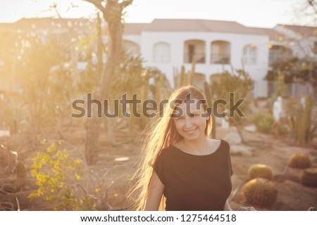 97e2cb5e16 Dreamy brunette young woman standing in cacti park wearing casual black  dress on sunset.Stylish