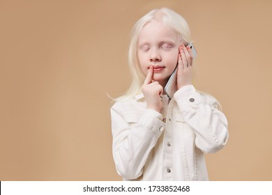 dreamy caucasian albino child talking on phone, attractive cute kid with unusual appearance stand with mobile phone, with eyes closed