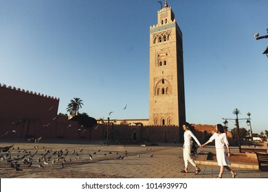 Dreamy couple dressed in white closes walks around African city Marrakesh in a sunny evening