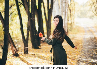 Dreamy dancing girl with long natural black hair on autumn background with trees and yellow leaves in bokeh. Inspired girl enjoys nature in autumn forest. Female beauty portrait among fallen foliage.