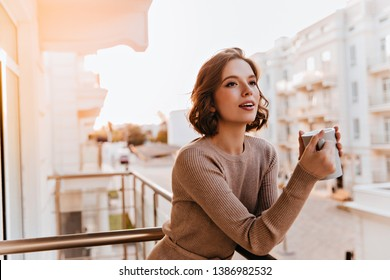 Dreamy dark-eyed girl drinking tea at balcony. Photo of caucasian well-dressed female model holding cup of coffee.