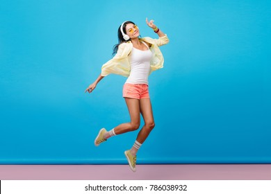 Dreamy dark-haired latin woman in casual colorful attire dancing in studio. Indoor photo of romantic young lady with happy face expression jumping in room with blue walls.