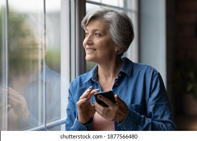 Dreamy elderly middle aged grey-haired woman looking out of window, holding mobile phone in hands. Happy older 60s lady, visualizing future, distracted from communicating online in social network.