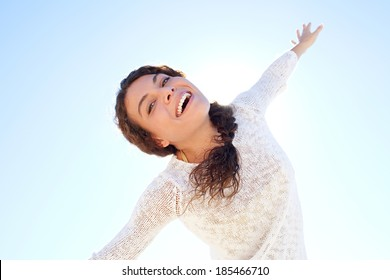Dreamy and ethereal portrait of an attractive young woman being playful and energetic dancing with her arms raised and smiling against a sunny blue sky. Healthy outdoors lifestyle.