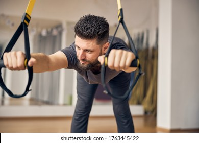 Dreamy flexible short-haired Caucasian male doing wide-stance hip hinge exercise at a gym