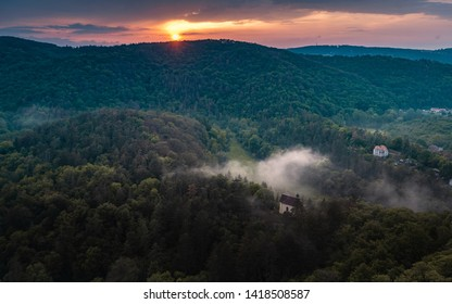 Dreamy forrest. Sunrise clouds. Forest hill. Autumn mist. Misty peaks. sunrise on top of rocky mountain with view into misty valley. Mountain view. Foggy mountain