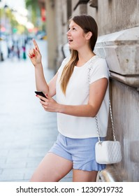 Dreamy girl leaning against edifice on city street using phone to find right address