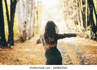 Dreamy girl with long natural black hair flies on autumn background with trees and yellow leaves in bokeh. Inspired girl enjoys nature in autumn forest. Beautiful girl among fallen foliage. Back view.
