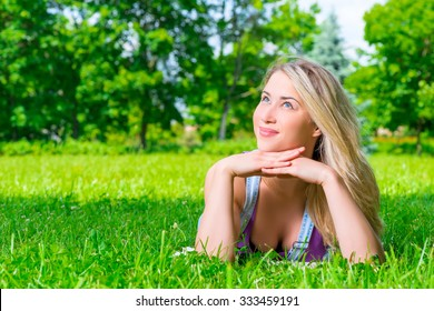 dreamy girl resting on the green grass in the park