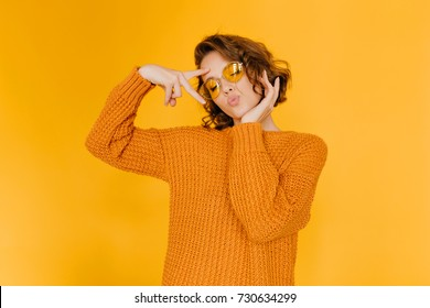Dreamy girl in trendy sweater posing with kiss face expression and eyes closed. Lovely short-haired lady in glasses enjoying photoshoot on yellow background.