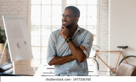 Dreamy happy african american black young business man looking away dreaming of good career think of successful startup strategy hoping for future opportunities goals stand in modern creative office
