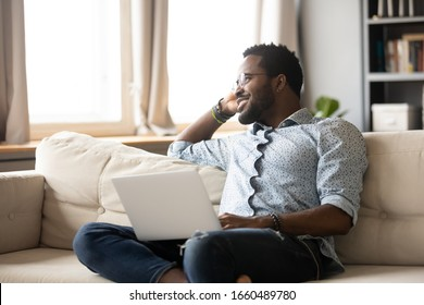 Dreamy happy young african ethnicity man sitting on sofa, holding laptop on knees, thinking of future challenges opportunities. Smiling positive millennial multiracial guy contemplating at window.