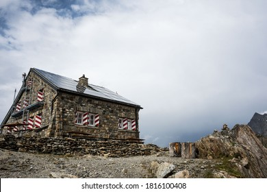 Dreamy Hiking hut hidden and in the Swiss Alps with cozy lights on and impressive rocks around it