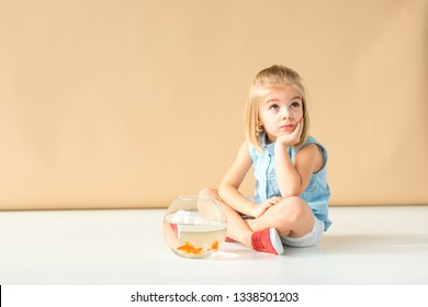dreamy kid sitting on floor with fishbowl and looking away on beige background