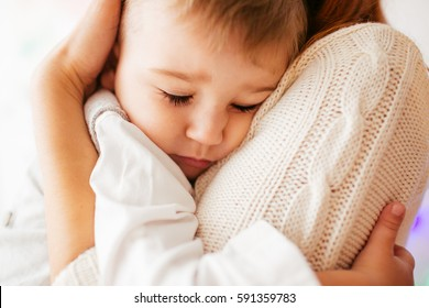 Dreamy little boy hugs his mother tightly sleeping on her shoulder