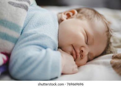 Dreamy little child sleeps under the blanket on a soft bed