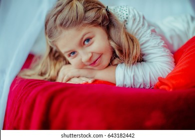 Dreamy little girl with blue eyes lies on red blanket