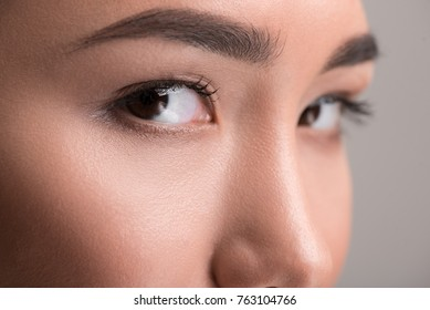 Dreamy look. Close-up of calm young asian female beautiful eyes are looking at camera thoughtfully. Isolated background