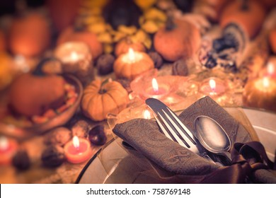Dreamy and Magical Fall Thanksgiving or Wedding Table Setting with Pumpkins, Silverware, Plate, Sunflower, and Candle Light.  Blur Bokeh for mood and room or space for your copy, text or design.