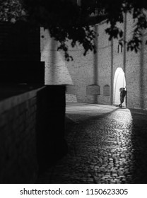 A dreamy man leans against the city wall