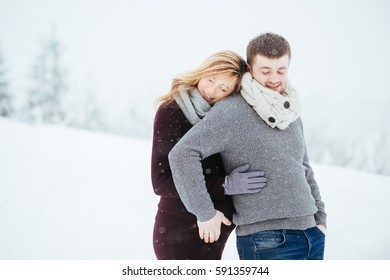 Dreamy man touches pregnant woman's belly tender while they stand under falling snow