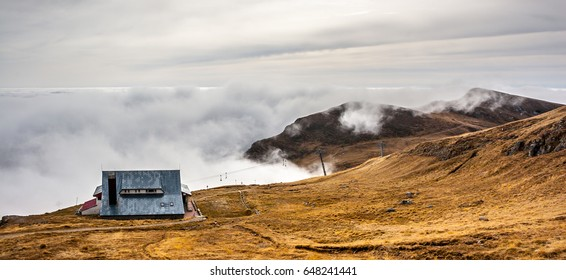 A dreamy mountain scene with a chalet and clouds cover on a mountain hill. Pastel colors sky in the background.