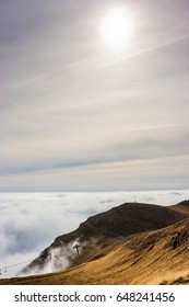 A dreamy mountain scene with clouds cover on a mountain hill. Pastel colors sky in the background.