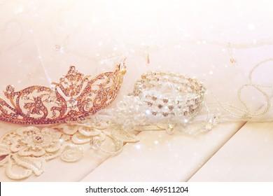 Dreamy photo of crystal jewellery and diamond tiara on toilette table. Selective focus. Glitter overlay