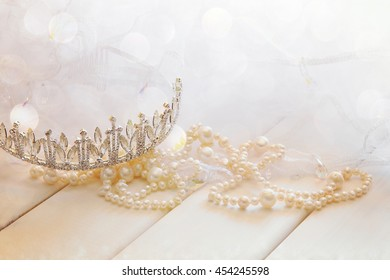Dreamy photo of white pearls necklace and diamond tiara on toilette table. Selective focus. Glitter overlay