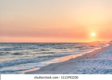 Dreamy pink peach orange sunset in Santa Rosa Beach, Florida with Pensacola coastline coast cityscape skyline in panhandle with ocean gulf mexico waves, birds