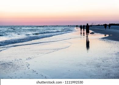 Dreamy pink peach orange sunset in Siesta Key, Sarasote, Florida with coastline coast ocean gulf mexico waves, beach shore