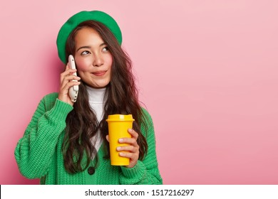 Dreamy pleasant looking Asian girl holds smartphone near ear, enjoys pleasant conversation while drinks coffee to go, has long dark hair, dressed in green stylish clothes, isolated on pink background,