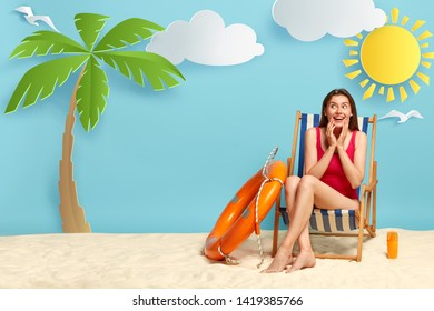 Dreamy positive woman enjoys hot day on coast, sits on deckchair, wears red bikini, uses suntan lotion to protect skin from sun, lifebuoy for save swimming, rejoices summer at seaside with palm, sun