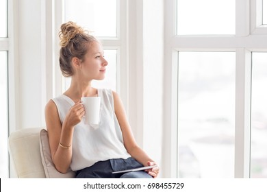Dreamy Pretty Woman With Tea and Tablet on Loggia
