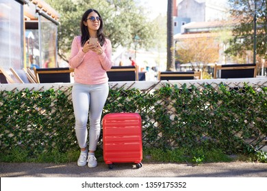 Dreamy pretty young woman texting message while waiting for bus. Beautiful Indian girl in sunglasses standing with red suitcase at bus station and using gadget. Tourist concept