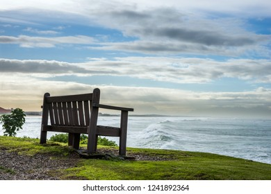 A dreamy resting place. Wooden bench on the wild ocean shore in the eveing.