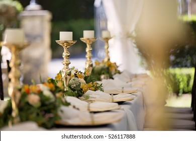 Dreamy and romantic wedding styling with candle holders, napkins and flowers.