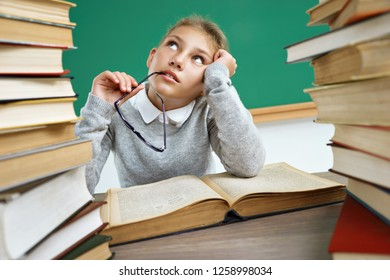 Dreamy school girl, looking up. Photo of little girl with open book, daydreaming or thinking of something. Education concept