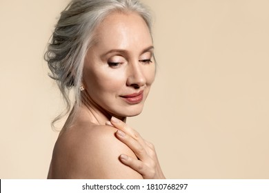 Dreamy  senior lady with perfect skin closeup portrait. Elderly woman touching naked shoulder looking aside down. Aged beauty procedure and body care. Maturity and wellness