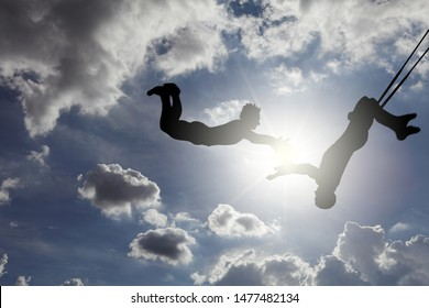 Dreamy silhouette of a pair of trapeze artists swinging through a blue cloudy sky.